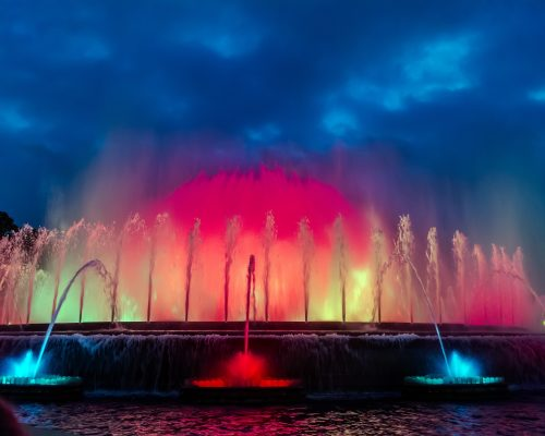Colorful performance of Magic Fountain of Montjuic in Barcelona, Spain. Show combines a spectacular display of music, water acrobatics and lights which generate over 50 kinds of shades and hues.