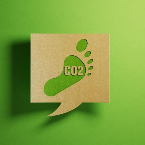 Carbon footprint icon on a chat bubble which is made of recycled paper on green background. Horizontal composition with copy space.